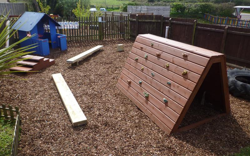 Outdoor play area with climbing wall